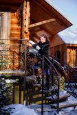 Girl in fur coat standing on stairs — Stockfoto