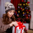 Suprised girl opening gift near the Christmas tree — Stock Photo