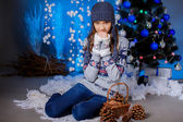 Girl near the Christmas tree with cones — Stock Photo