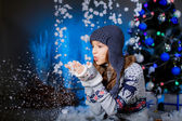 Girl near the Christmas tree blows snow — Stock Photo