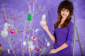 Girl in a hat decorating Christmas tree — Stock Photo