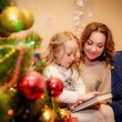 Mother with her daughter reading a book in the New Year's Eve — Stock Photo