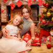 Mother and daughter near a Christmas tree — Stock Photo
