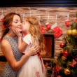 Little girl kissing her mother on New Year background — Zdjęcie stockowe
