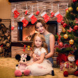 Mother and daughter sitting near a Christmas tree — Foto Stock