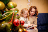 Mother with her daughter reading a book in the New Year's Eve — Стоковое фото