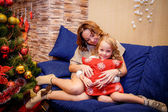 Mother and daughter sitting on the sofa near the Christmas tree — Stock Photo