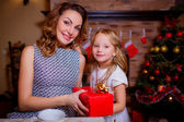 Mother and daughter with a gift at the table with tea — Photo
