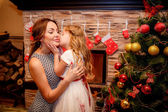 Little girl kissing her mother on New Year background — Stock Photo