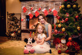 Mother and daughter sitting near a Christmas tree — Stockfoto