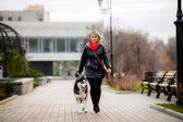 Woman walking dog in park — Stock Photo