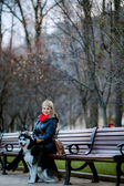 Woman and dog sitting on bench — Stockfoto