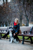 Woman and dog sitting on bench — Photo