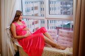Pregnant woman on windowsill — Foto de Stock