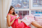 Pregnant woman looking at baby clothes — Stock Photo