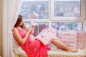 Mulher grávida, a olhar para a roupa do bebê — Foto Stock