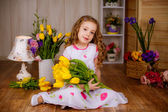 Smiling girl with tulips at home — Stock Photo