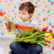 Boy sitting with tulips — Stock Photo #41381715