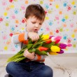Beautiful boy with tulips — Stock Photo