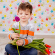 Boy sitting with tulips — Stock Photo #41381725