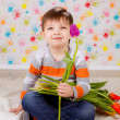 Boy sitting with tulips — Stock Photo #41381771