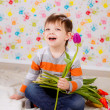 Boy sitting with tulips — Stock Photo