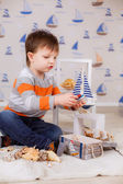 Boy holds wooden ship — Stock Photo
