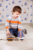 Boy holds ship with paper sails — Stock Photo