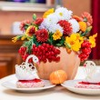 Chrysanthemums and cakes in the shape of swans — Stock Photo
