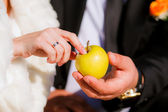 Apple in the hands of the bride and groom — Stock Photo