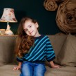 Little girl sitting on the couch — Stock Photo