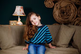 Little girl sitting on the couch — Stockfoto