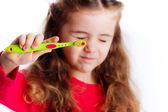 Little girl showing a toothbrush — Stockfoto