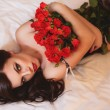 Woman with red roses lying on the bed. — Stock Photo