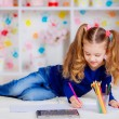 Happy little girl draws with colored pencils — Stock Photo #43542987