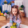 Little girl holding the flowers in the pot — Stock Photo