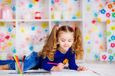 Happy little girl draws with colored pencils — Stockfoto