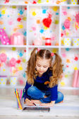 Happy little girl draws with colored pencils — Stock Photo