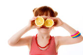 Little girl closes her eyes with oranges — Foto Stock