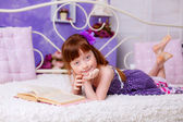 Red-haired girl reading a book on bed — Stockfoto