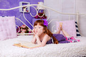 Red-haired girl reading a book on bed — Stock Photo