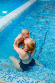 Mother kissing her son in the pool — Stock Photo