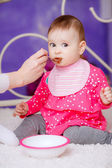 Mother spoon feeding her cute baby girl — Stock Photo