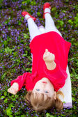 Girl  lying on the grass and  pointing at the camera — Stock Photo