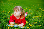 Little girl reading a book on the grass — Stock Photo