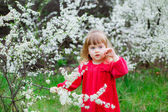 Little girl  near the  flowering branches — Stock Photo