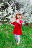 Petite fille près des branches fleuries — Photo
