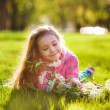 Girl lying on the grass with a bouquet of lilacs — Stock Photo #45315705