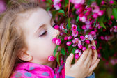 Girl smelling a flowering tree — Foto Stock