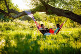 Couple in  hammock playing the guitar. — Stock Photo